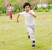 Boy running ahead in a field with girl catching up behind